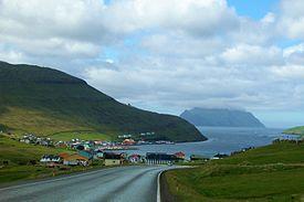 Bilväg ner till byn. Den lilla ön Mykines skymtar även i bakgrunden.